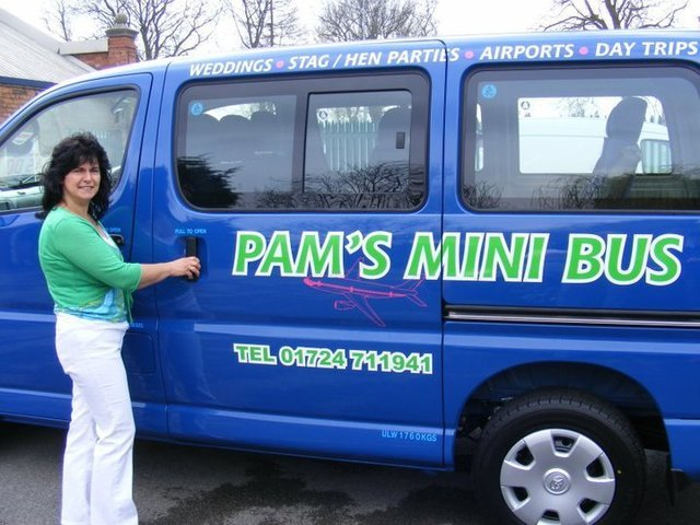 Pam standing in front of her blue mini bus